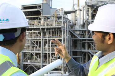 two engineer  discussing a new project with large oil refinery background
